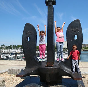 Three small children playing on large anchor at Hingham Shipyard Marina near Seascape at Weymouth
